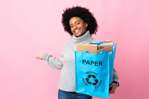 Young african american woman holding a recycle bag isolated on colorful wall extending hands to the side for inviting to come