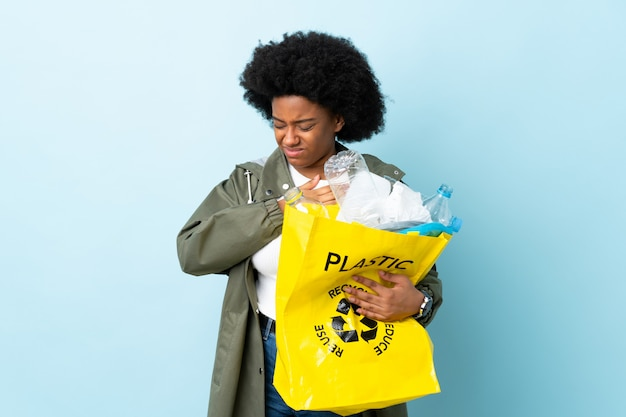 Young african american woman holding a recycle bag isolated on colorful wall having a pain in the heart