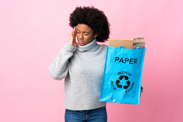 Young african american woman holding a recycle bag isolated on colorful with headache