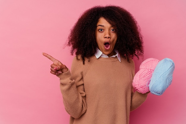 Young african american woman holding a sewing threads isolated on pink background pointing to the side