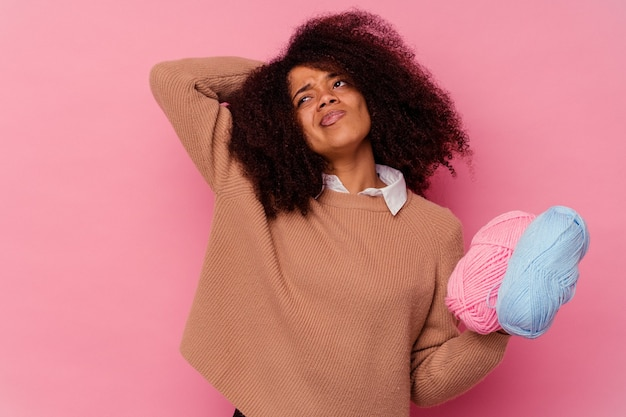Young african american woman holding a sewing threads isolated on pink background touching back of head, thinking and making a choice.