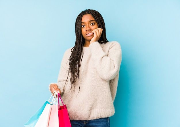 Young african american woman holding a shopping bag isolated biting fingernails, nervous and very anxious.
