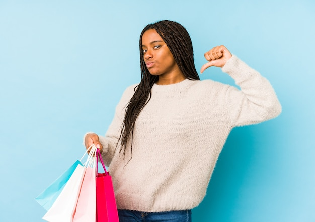 Young african american woman holding a shopping bag isolated feels proud and self confident, example to follow.