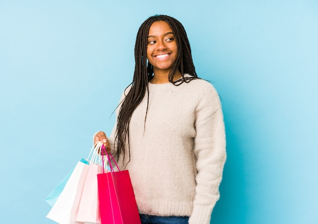 Young african american woman holding a shopping bag isolated looks aside smiling, cheerful and pleasant.