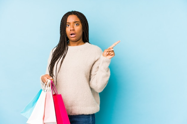 Young african american woman holding a shopping bag isolated pointing to the side