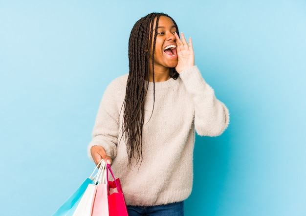 Young african american woman holding a shopping bag isolated shouting and holding palm near opened mouth.