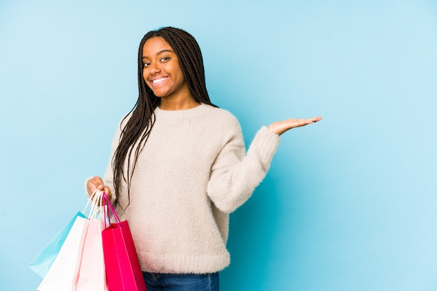 Young african american woman holding a shopping bag showing a copy space on a palm and holding another hand on waist.