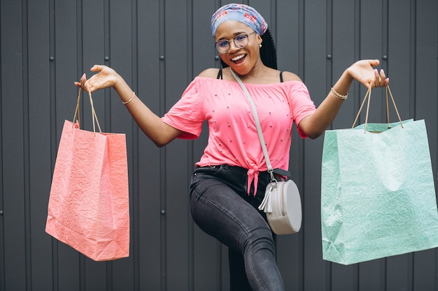 Young african american woman holding shopping bags at the gray wall