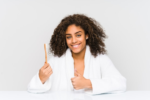 Young african american woman holding a toothbrush smiling and raising thumb up