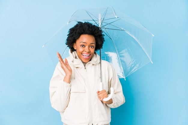 Young african american woman holding an umbrella isolated surprised and shocked.
