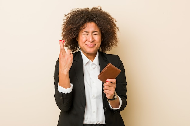 Young african american woman holding a wallet crossing fingers for having luck
