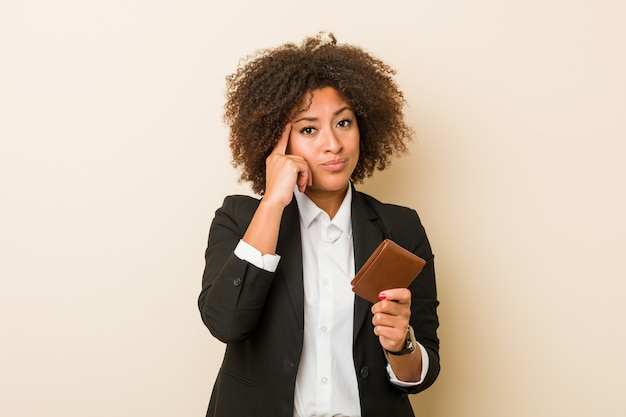 Young african american woman holding a wallet pointing his temple with finger, thinking, focused on a task.