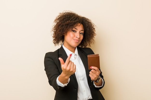 Young african american woman holding a wallet pointing with finger at you as if inviting come closer.
