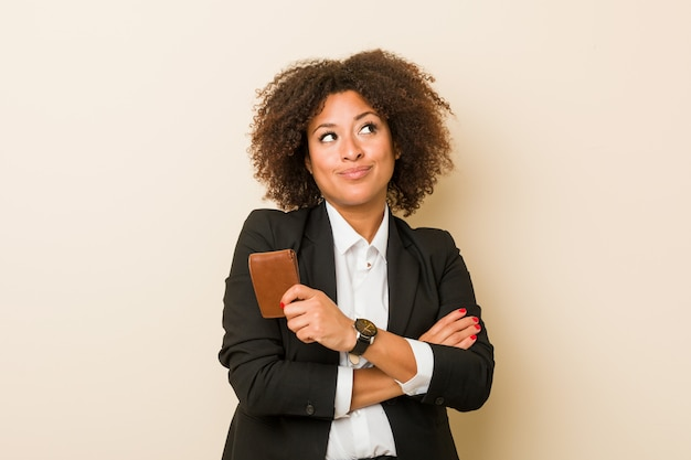 Young african american woman holding a wallet smiling confident with crossed arms.