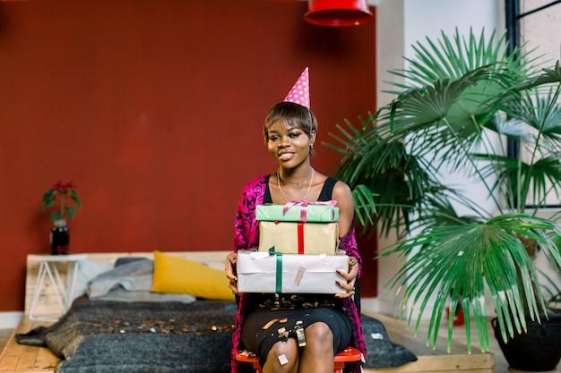 선물 상자를 들고 생일 모자에있는 젊은 아프리카 계 미국인 여자