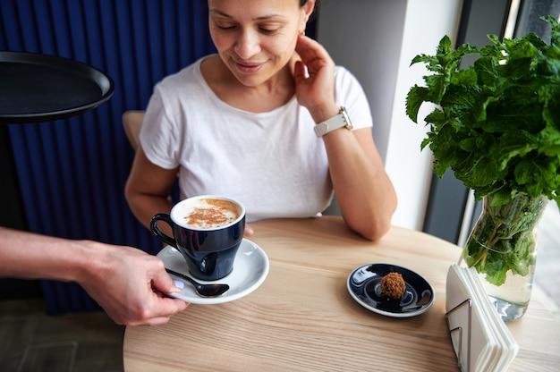 彼女に仕えるウェイトレスの手でカプチーノのカップを見ているカフェで若いアフリカ系アメリカ人の女性