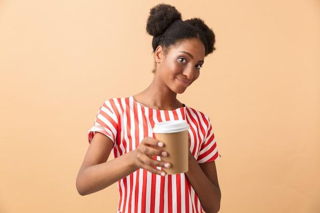 テイクアウトコーヒーと紙コップを保持しているカジュアルな服装の若いアフリカ系アメリカ人女性、孤立