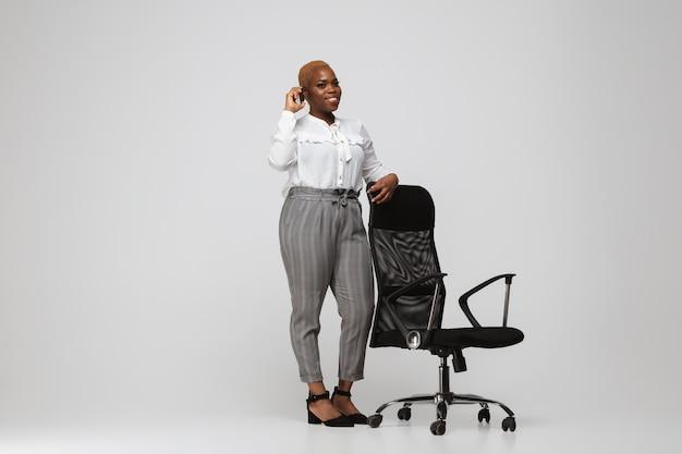 회색 배경에 평상복을 입은 젊은 아프리카계 미국인 여성