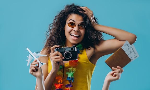 Молодая афро-американская женщина в солнцезащитных очках держит ретро-камеру с цветком гавайских лей