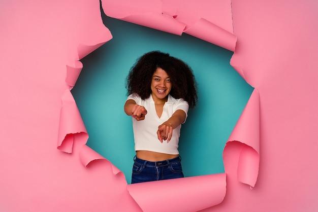 찢어진 된 종이 파란색 배경에 고립에서 젊은 아프리카 계 미국인 여자 앞을 가리키는 밝은 미소.