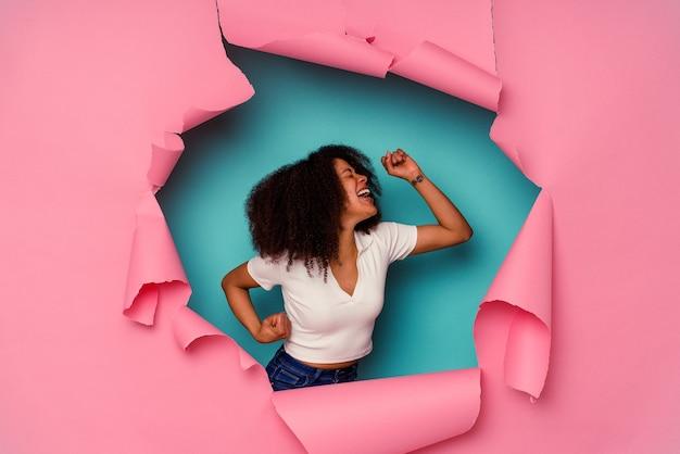 勝利、勝者の概念の後に拳を上げる青い背景で隔離の破れた紙の若いアフリカ系アメリカ人女性。