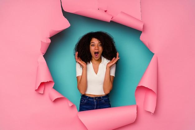 青い背景に分離された破れた紙の若いアフリカ系アメリカ人女性は驚いてショックを受けました。