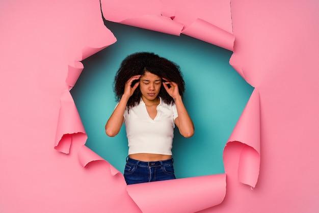 Молодая афро-американская женщина в рваной бумаге, изолированной на синем фоне, трогательно висках и имея головную боль.