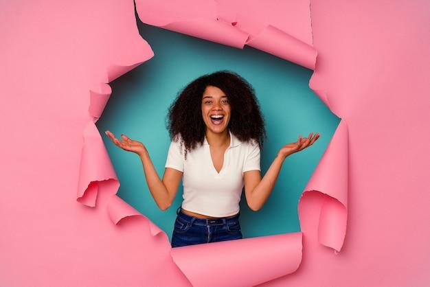 青で隔離された破れた紙の若いアフリカ系アメリカ人の女性は、嬉しい驚きを受け取り、興奮し、手を上げます。