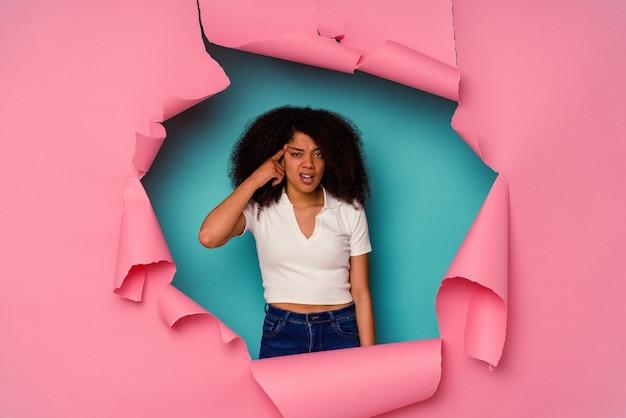 人差し指で失望のジェスチャーを示す青で分離された破れた紙の若いアフリカ系アメリカ人女性。
