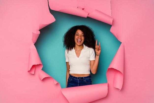 革命の概念として角のジェスチャーを示す青で分離された破れた紙の若いアフリカ系アメリカ人の女性。