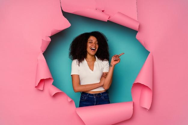 引き裂かれた紙の若いアフリカ系アメリカ人女性は、人差し指を離れて元気に指して青い笑顔で隔離。