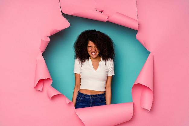 青い壁に隔離された破れた紙の若いアフリカ系アメリカ人女性は笑って目を閉じ、リラックスして幸せを感じます。