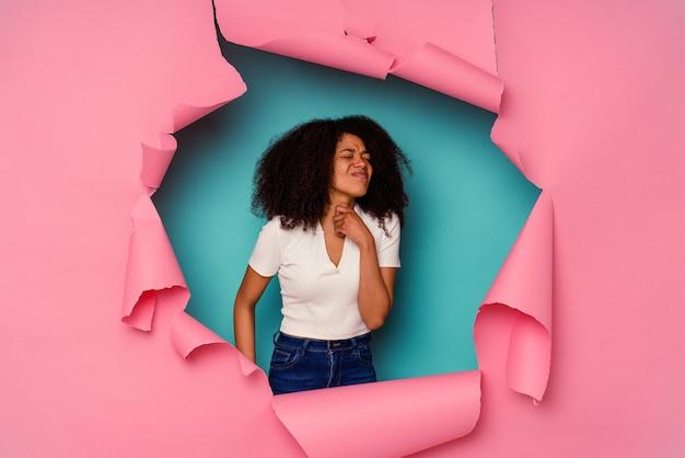 青い壁に分離された破れた紙の若いアフリカ系アメリカ人女性は、ウイルスや感染症のために喉の痛みに苦しんでいます。