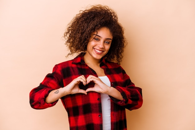 Young african american woman isolated on beige wall smiling and showing a heart shape with hands.