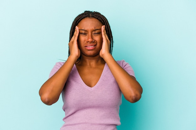 Young african american woman isolated on blue background  having a head ache, touching front of the face.