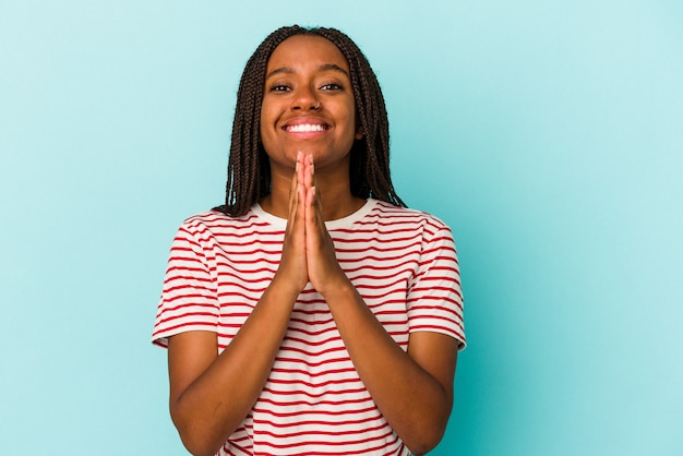 Young african american woman isolated on blue background  holding hands in pray near mouth, feels confident.