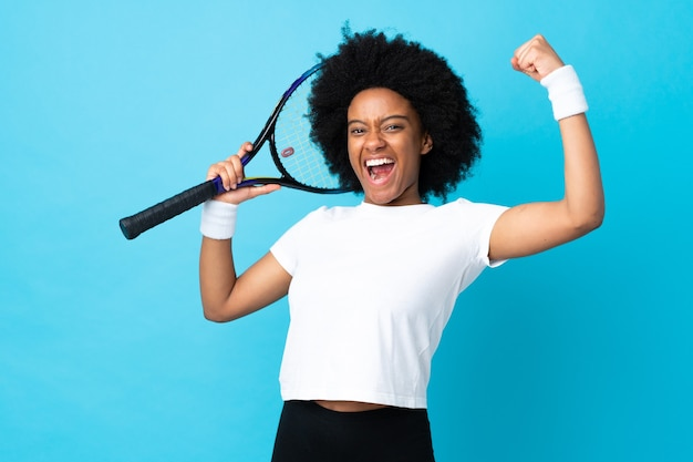 Young african american woman isolated on blue background playing tennis and celebrating a victory
