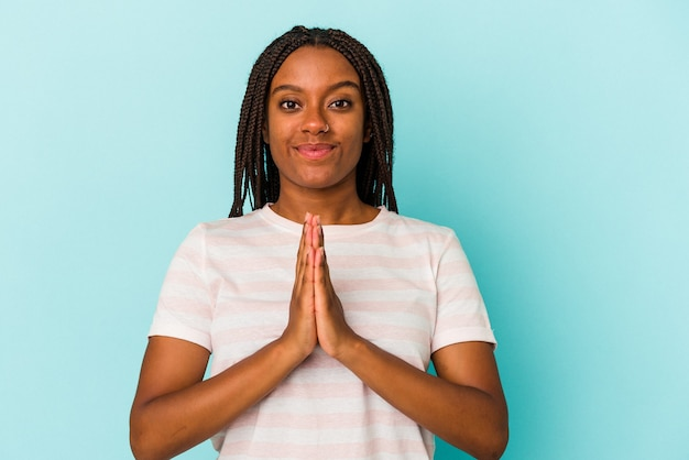 Young african american woman isolated on blue background  praying, showing devotion, religious person looking for divine inspiration.