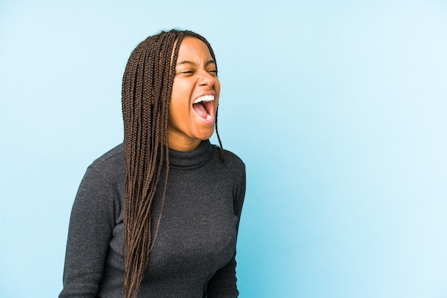 Young african american woman isolated on blue background shouting towards a copy space