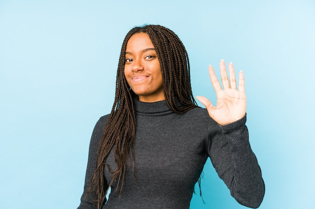 Young african american woman isolated on blue background smiling cheerful showing number five with fingers.