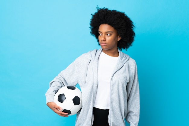 Young african american woman isolated on blue background with soccer ball