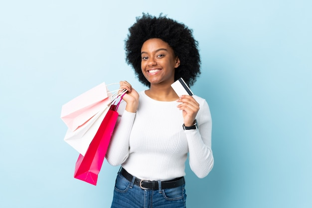Young african american woman isolated on blue holding shopping bags and a credit card