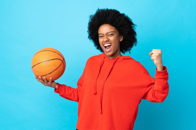 Young african american woman isolated on blue playing basketball