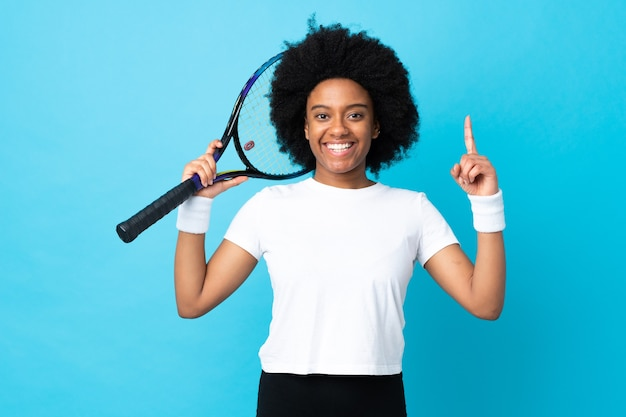 Young african american woman isolated on blue playing tennis and pointing up