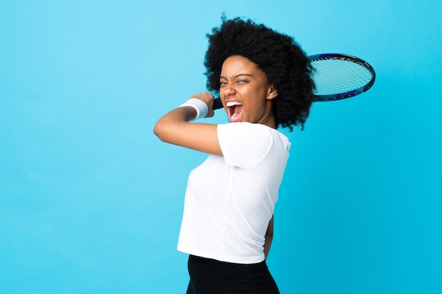 Young african american woman isolated on blue playing tennis