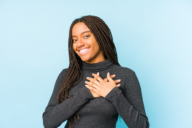 Young african american woman isolated on blue wall has friendly expression, pressing palm to chest. love concept.