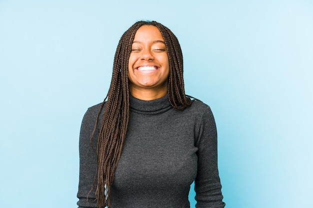 Young african american woman isolated on blue wall laughs and closes eyes, feels relaxed and happy.