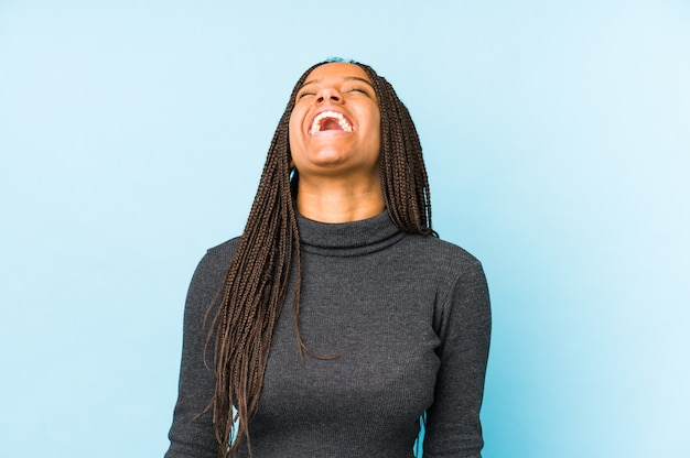 Young african american woman isolated on blue wall relaxed and happy laughing, neck stretched showing teeth.