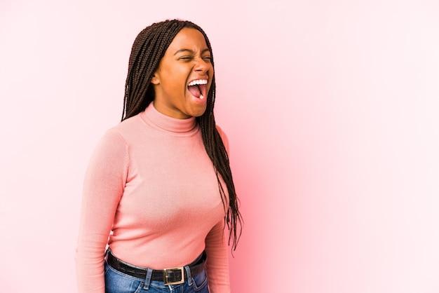 Молодая афро-американская женщина, изолированная на розовой поверхности, кричит в сторону копии пространства