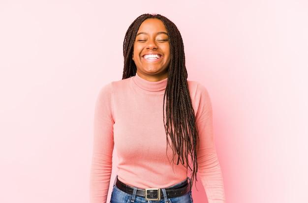 Молодая афро-американская женщина изолированная на розовой стене смеется и закрывает глаза, чувствует ослабленным и счастливым.